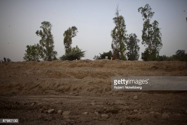 People living in a slum area stand over a newly dug roadway April 21 2009 where members of twelve families have been farming and living for four...