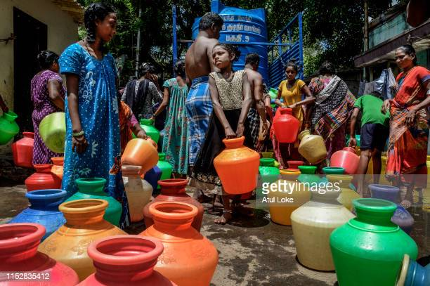 people living slum settlement from heart of the Chennai city gather near the Metro water supply tanker to collect the water for their daily usage on...