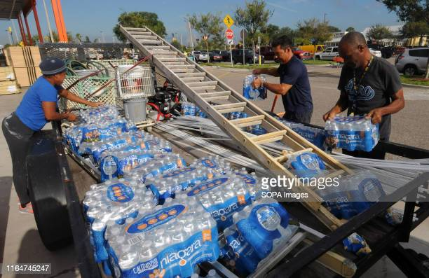 People load cartons of bottled water onto a trailer in a Home Depot parking lot in preparation for the arrival of Hurricane Dorian which is expected...