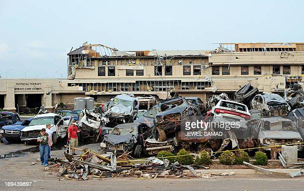 People look a pile of twisted cars at a hospital in tornadodevastated Moore Oklahoma on May 24 2013 The tornado one of the most powerful in recent...