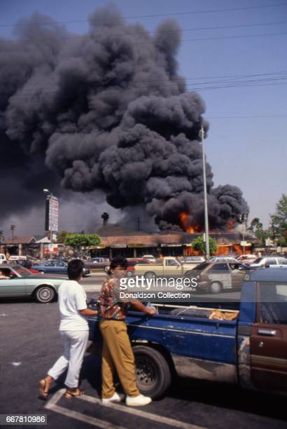 People look across the street from Viva Shopping center amongst a billowing fire during widespread riots that erupted after the acquittal of 4 LAPD...