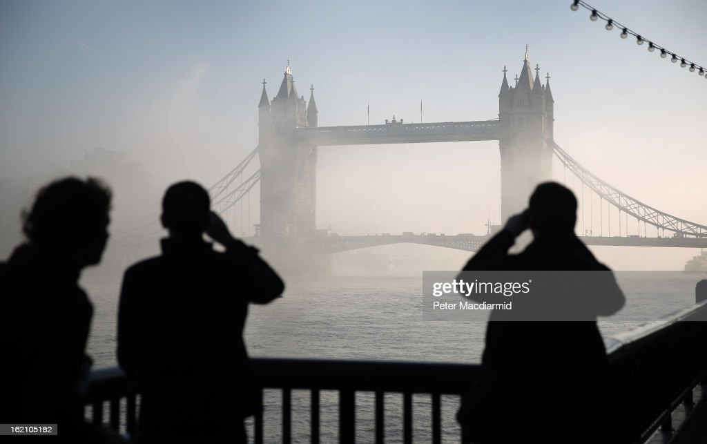 People look and photograph Tower Bridge as it emerges from early morning fog on The River Thames on February 19, 2013 in London, England. Heathrow was forced to cancel a number of flights and London City Airport suffered distruptions as a result of poor visibility due to fog.