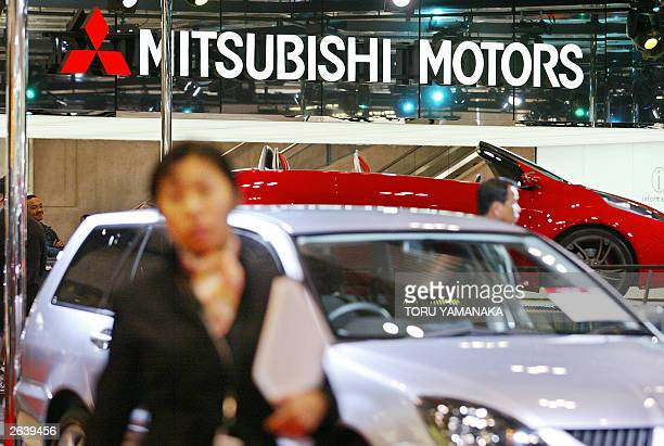 People look around vehicles at a booth of Japan's Mitsubishi Motors during the preview of Tokyo Motor Show in Makuhari suburban Tokyo 24 October 2003...