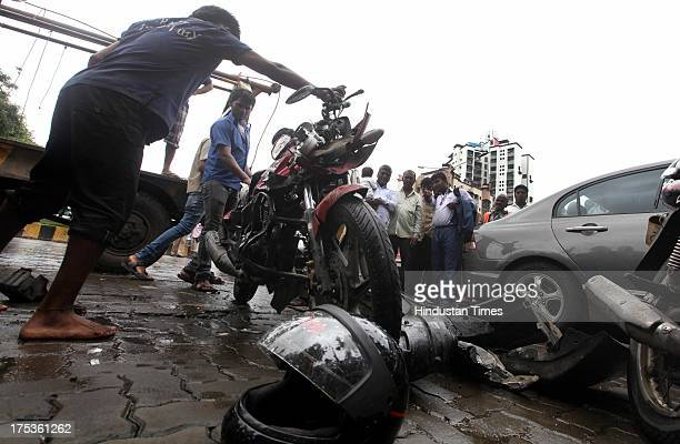 People look as police inspect the damaged car and bikes which met with an accident at Linking Road Kandivali on August 2 2013 in Mumbai India Indian...
