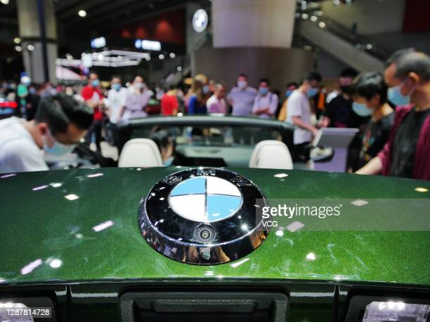 People look at a BMW 4 series car during the 18th Guangzhou International Automobile Exhibition at China Import and Export Fair Complex on November...