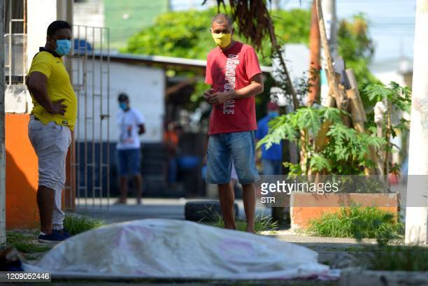 TOPSHOT People look at a body said to be laying for three days oustide a clinic in Guayaquil Ecuador on April 3 2020 Troops and police in Ecuador...