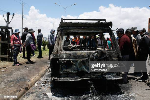 People look at a burned car in the road to the Senkata Fuel Plant on November 20 2019 in El Alto outskirts of La Paz Bolivia At least six people were...