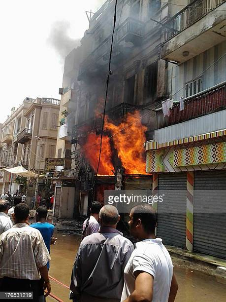 People look at a burning building close to a church after being torched by unknown assailants in the central Egyptian city of Minya on August 14,...