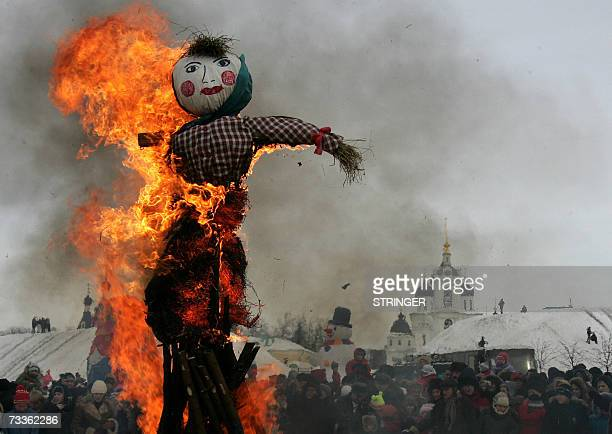 People look at a burning scarecrow as they take part in a tradition Orthodox Shrovetide celebration in Russia's town of Dmitrov located some 60km...