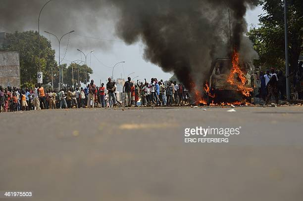 People look at a car transporting two children of an exSeleka colonel and which was set on fire at the 'UN crossroad'' on January 12 2014 In Bangui...