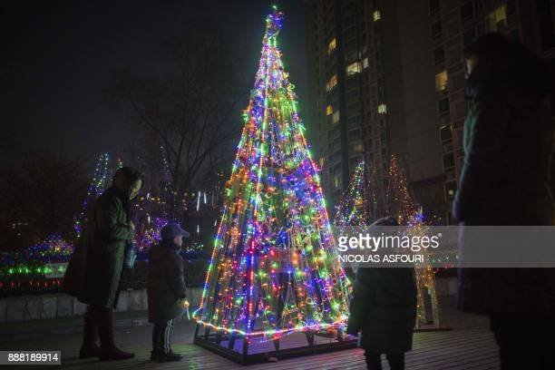 TOPSHOT People look at a Christmas tree decorated with colourful lights at a residential compound in beijing on December 8 2017 / AFP PHOTO / NICOLAS...