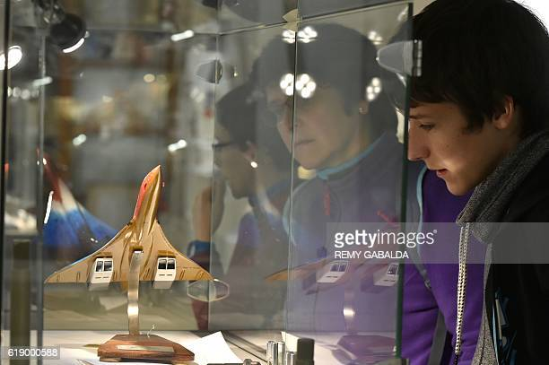 People look at a Concorde plane model at the Saint Aubin Auction House in Toulouse on October 28 ahead of an auction of Concorde items as mechanical...