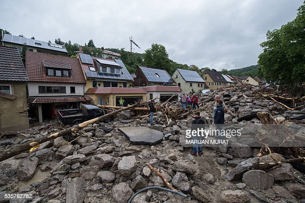 TOPSHOT People look at a damaged street on May 30 2016 in Braunsbach following a heavy storm At least four people died and several more were injured...