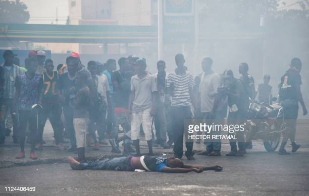 People look at a dead demonstrator shot by police during clashes in the center of Haitian Capital PortauPrince February 12 on the sixth day of...