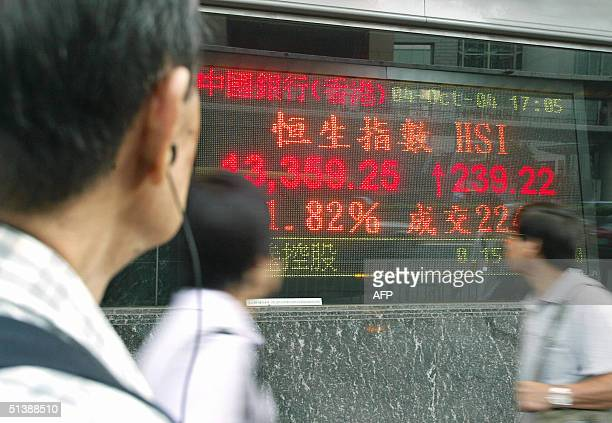 People look at a digital screen which shows a result of the Heng Seng Index closed up 239.22 points at 13,359.25 in Hong Kong on 04 October 2004....