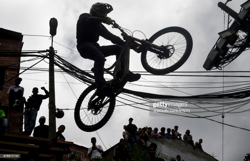 TOPSHOT - People look at a downhill rider during the Urban Bike Inder Medellin race final at the Comuna 1 shantytown in Medellin, Antioquia department, Colombia on November 19, 2017. /
