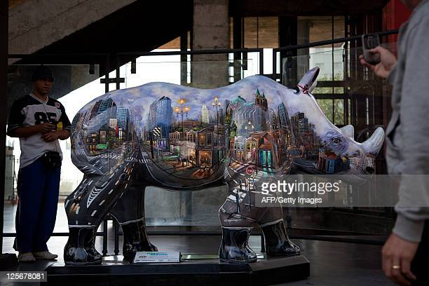 People look at a fiberglassmade rhinoceros with a view of the city of Sao Paulo painted on it on display in front of the Art Museum of Sao Paulo as a...