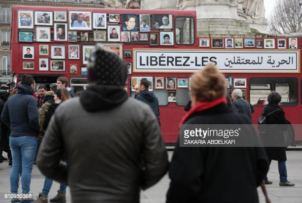 People look at a 'Freedom Bus' displaying portraits of people detained or missing after it was driven onto the Place de la Republique in Paris on...