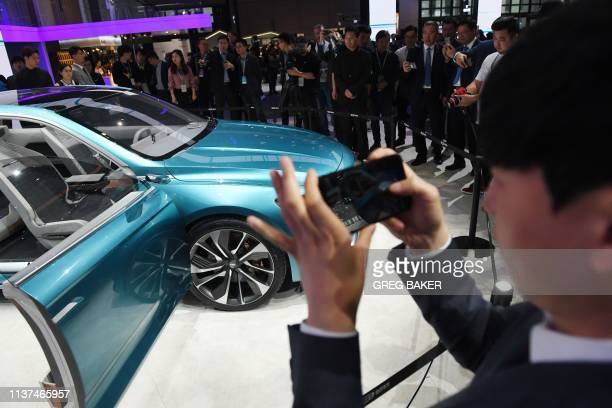 People look at a Geely Preface on the opening day of the Shanghai Auto Show on April 16 2019 Global car makers flock to the Shanghai Auto Show this...