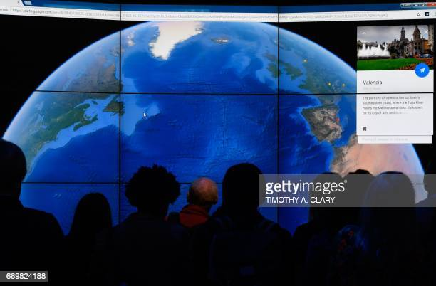 People look at a Google Earth map on a screen as Google Earth unveils the revamped version of the application April 18 2017 at a event at New York's...