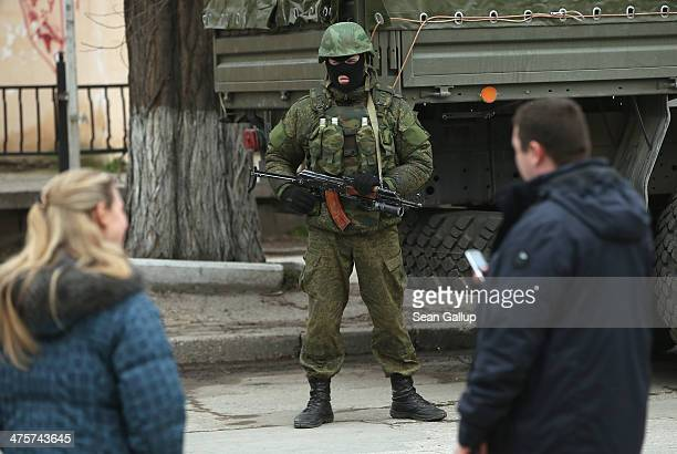 People look at a heavilyarmed soldier displaying no identifying insignia in a street in the city center on March 1 2014 in Simferopol Ukraine...
