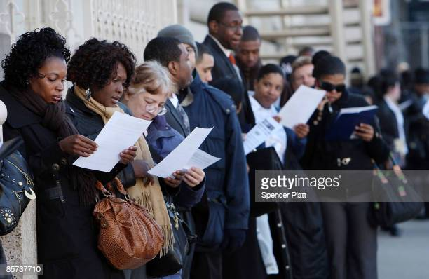 People look at a job offers handed out to them as they wait in line to get into the Brooklyn Diversity Career Fair at the Brooklyn Academy of Music...