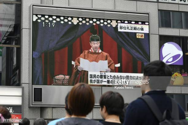People look at a large television screen in Osaka's Dotonbori entertainment district on Oct 22 showing a live broadcast of a ceremony in which...