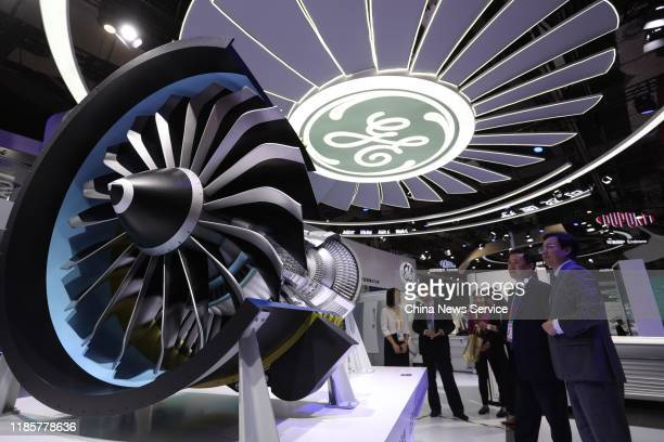 People look at a LEAP engine demonstration model from General Electric Company on day one of the 2nd China International Import Expo at the National...