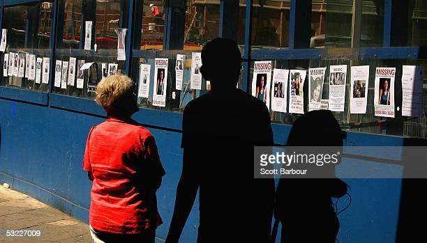 People look at a long line of missing people posters placed by friends and relatives after the London bombings outside of King's Cross railway...