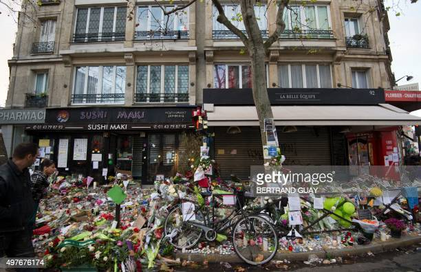 People look at a makeshift in front of a Japanese restaurant and the Cafe Belle Equipe, two of the site of the attacks at rue de Charonne in the 11th...