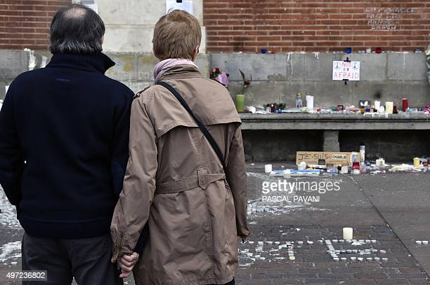 People look at a makeshift memorial at the place du Capitole in Toulouse on November 15 after a series of gun attacks occurred across the city AFP...
