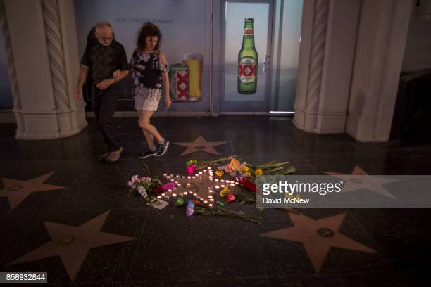 People look at a makeshift memorial at the Tom Petty and the Heartbreakers star on The Hollywood Walk of Fame on October 2 2017 in Los Angeles...