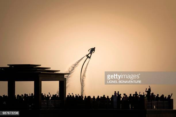 People look at a man performing on a waterpropelled flyboard during the BMX freestyle parc pro final on March 24 2018 in Jeddah during a two days...