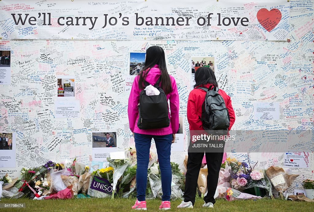 People look at a memorial to murdered Labour MP, Jo Cox is pictured outside the Houses of Parliament in London on June 20, 2016. / AFP / JUSTIN