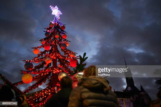 People look at a merrygoround like a Christmas tree A Christmas market is placed on the main square of Toulouse the Capitole People come to buy a hot...