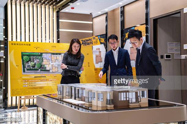 People look at a model of the Downtown 38 residential project developed by Sun Hung Kai Properties Ltd at a showroom for the development in Hong Kong...