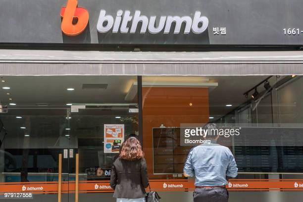 People look at a monitor displaying the prices of cryptocurrencies at a Bithumb exchange office in Seoul South Korea on Wednesday June 20 2018...
