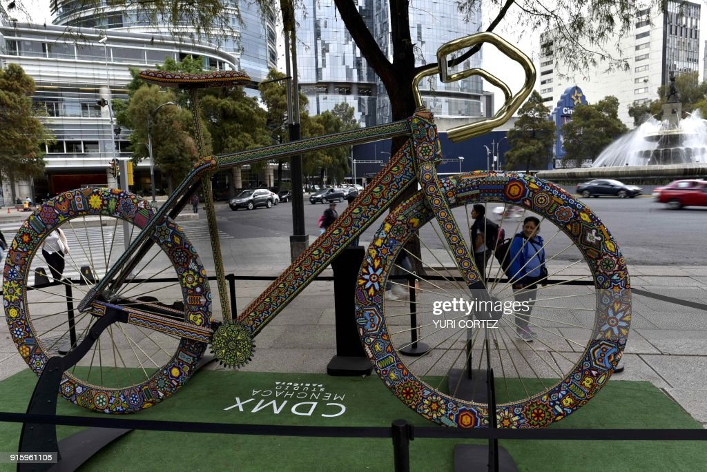 People look at a monumental sculpture of a bicycle called 'Iwarika Nautsarika' ('Winning a Race') made of fiberglass, wood and with a bronze handlebar banded in gold, worked in Huichol art and placed along Reforma avenue as part of an exposition called 'the world's biggest Huichol exhibit', in Mexico City, on February 8, 2018. One hundred Wixarikas indigenous artists from the social and cultural company Paricuta made 10 monumental works of art inspired by sports and nature, which were put on public display on the street. /