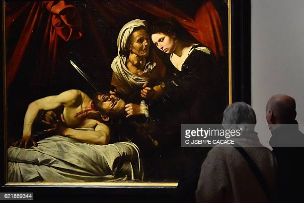 People look at a painting believed to be the 'Judith Beheading Holofernes' by Italian artist Michelangelo Merisi da Caravaggio presented along with a...