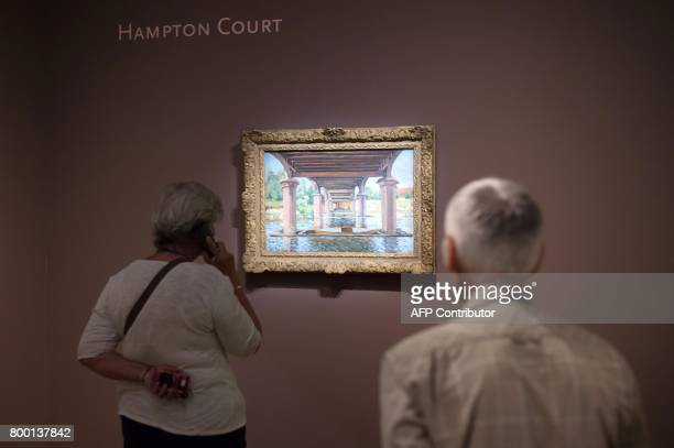 People look at a painting entitled 'Sous le pont d'Hampton Court' by late French painter Alfred Sisley as part of the exhibition 'Sisley the...