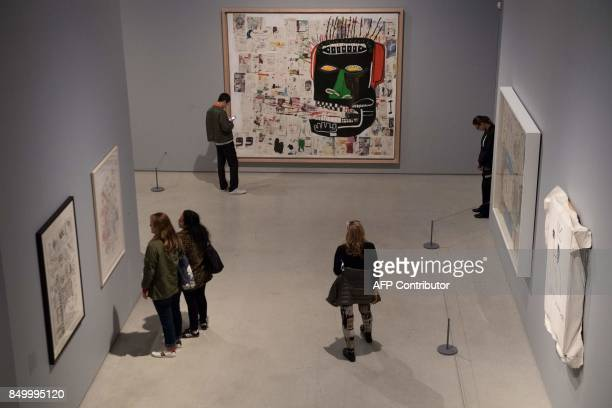 People look at a painting titled 'Glenn' by US artist Jean Michel Basquiat during a press call for a new exhibition Basquiat Boom for real at the...
