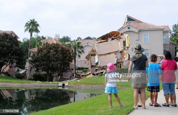 People look at a partially collapsed building over a sinkhole at Summer Bay Resort near Disney World on August 12 2013 in Clermont Florida The 40 to...
