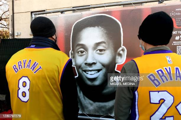 People look at a photo exposition showing a boy Kobe during the inauguration ceremony of a square named after late Los Angeles Lakers basketball star...
