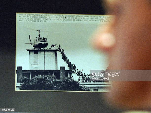 People look at a picture showing the 1975 fall of Saigon by Hugh Van Es on the wall at the Foreign Correspondents' Club in Hong Kong on May 15 2009...