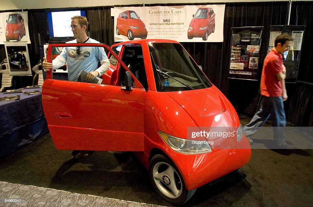 People Look At A Plug In Electric Tango Commuter Car At The