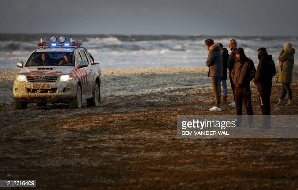 People look at a police car on a beach after a group of surfers was reported in trouble at the Noordelijk Havenhoofd, near the coastal town of...