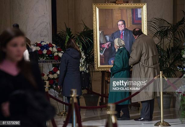 People look at a portrait of US Supreme Court Justice Antonin Scalia in Washington DC on February 19 2016 as he lies in repose at the Supreme Court...