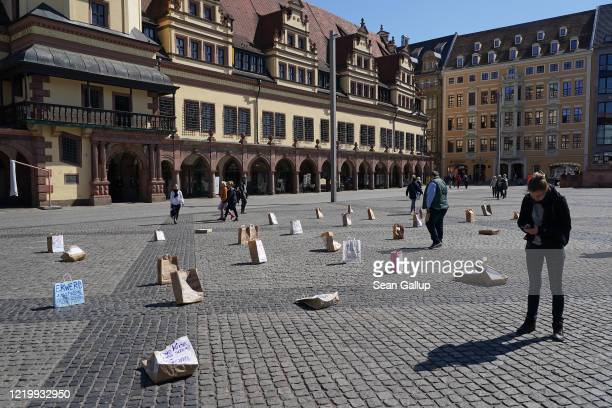 People look at a protest installation of socially-distanced shopping bags to demand more state support for the self-employed during the novel...