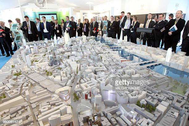 People look at a scale model of London architectural project at a stand during the 21st edition of the international MIPIM property trade show on...