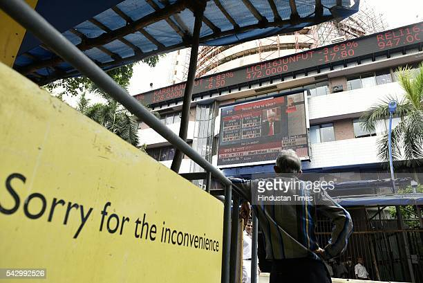 People look at a screen across a road displaying the Sensex on the facade of the Bombay Stock Exchange building after Britain's exit from the...